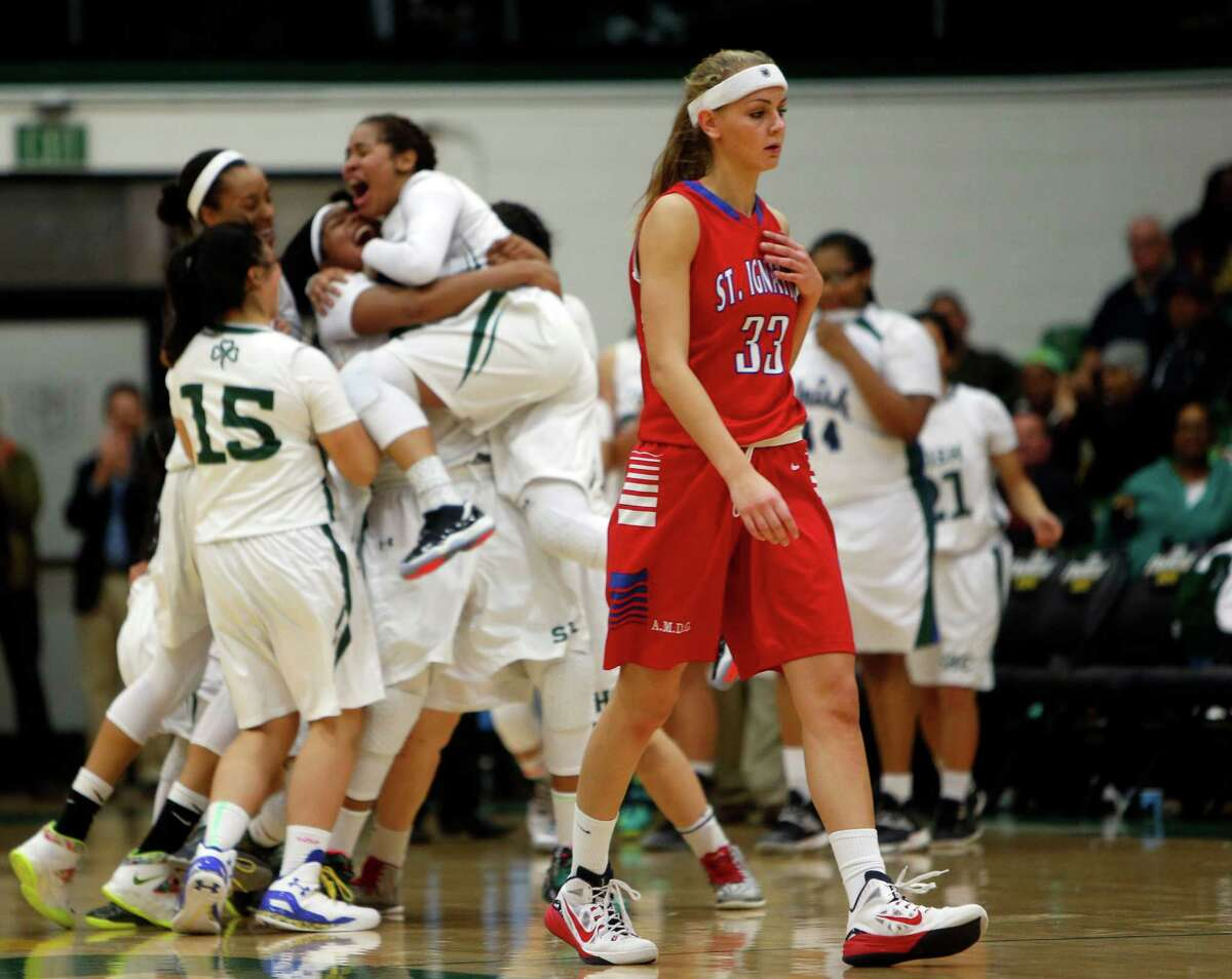 St. Ignatius' Josie Little walks off the court as 14th-ranked Sacred Heart Cathedral celebrates its 60-50 win at Memorial Gym. The Irish never trailed.