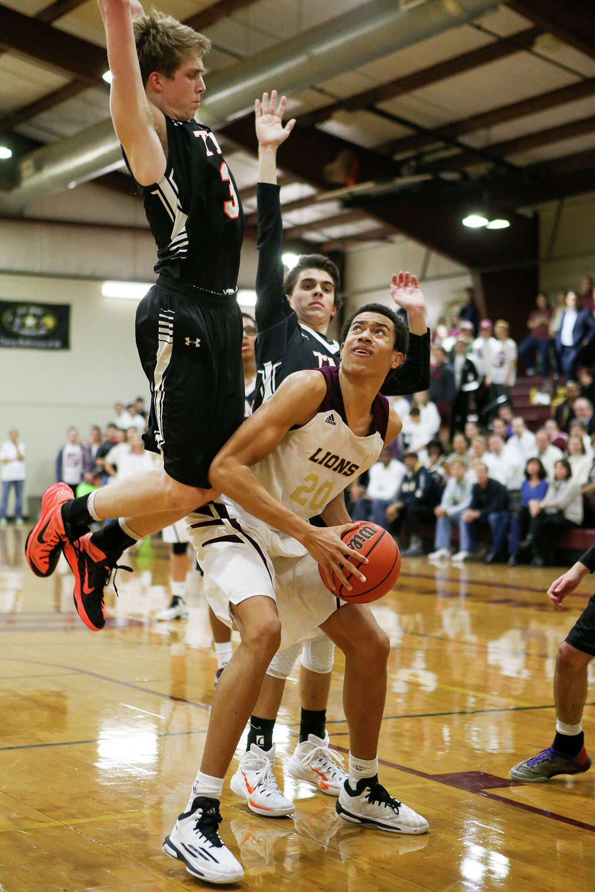 San Antonio Christian's Justin Rpbinsin (right) looks for a way to the basket past Nelson Black (left) and Collin Peterson of TMI during the first second half of their TAPPS 4-4A game at San Antonio Christian on Tuesday, Jan 13, 2015. San Antonio Christian beat TMI 51-45. MARVIN PFEIFFER/ mpfeiffer@express-news.net