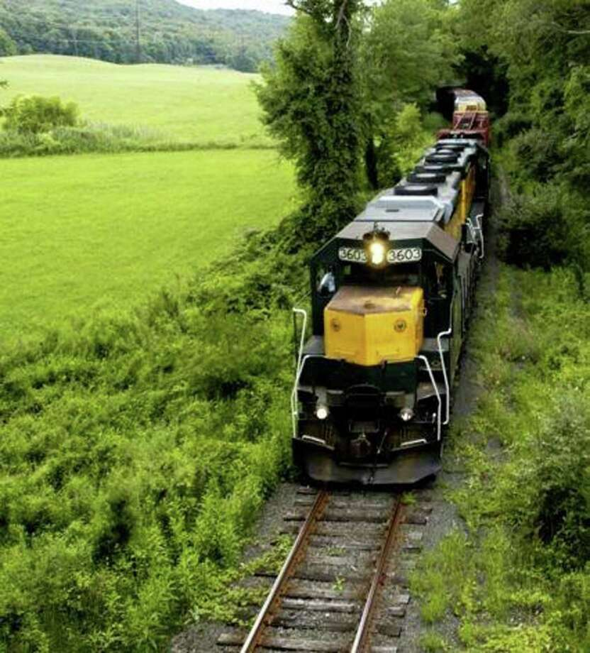 A Housatonic Railroad freight train chugs northward in the Lanesville district of New Milford in recent years along a route many hope will again serve to deliver commuters, tourists and other travelers to and from Danbury and points south. Photo: Norm Cummings / The News-Times