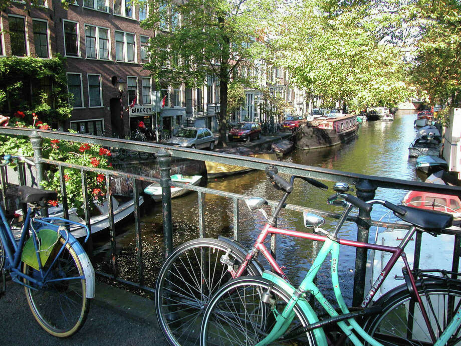 Pedal your way around Amsterdam to take in copious canal views. Photo: Rick Steves / © Rick Steves' Europe  (www.ricksteves.com)