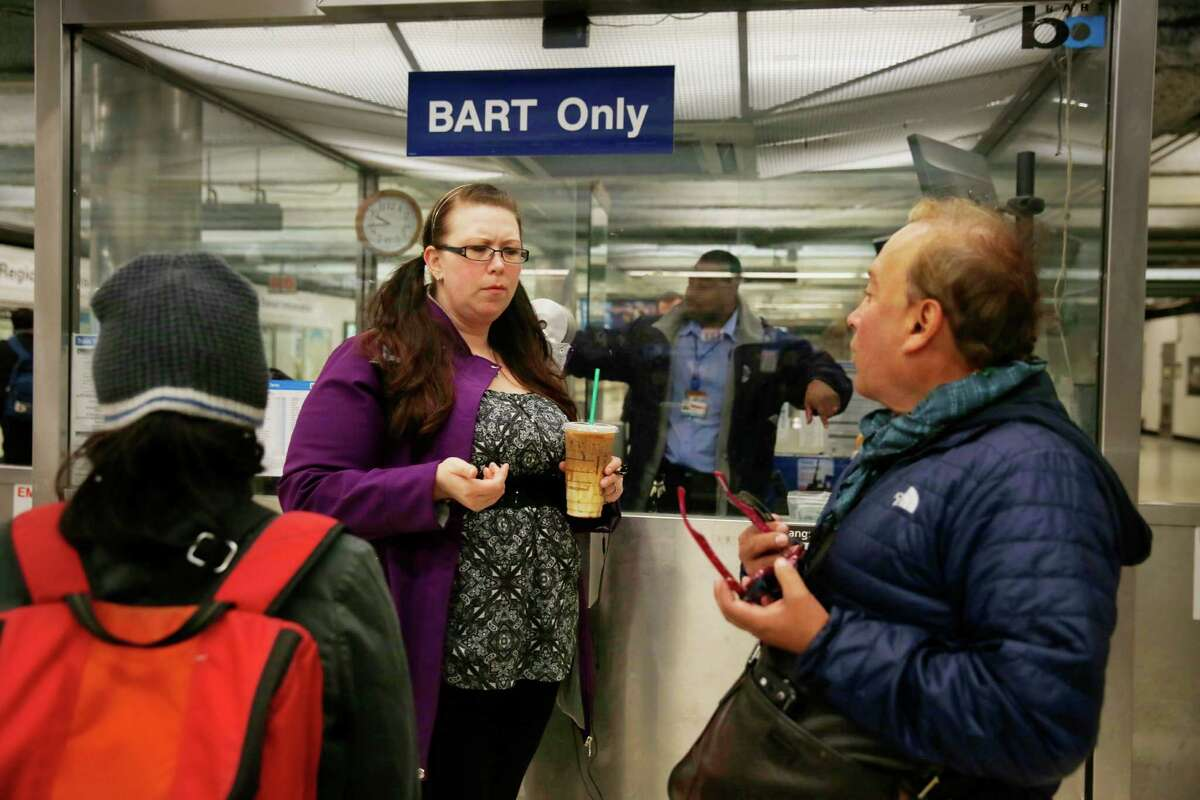 (Left to right) Chelsea Martin of San Mateo, gives Carlos Sota of Venezuela some help on how to get to alternative public transportation at the closed Powell Street BART station on Wednesday, January 14, 2014 in San Francisco, Calif. The Powell Street BART station was temporarily closed after a man jumped in front of train on Wednesday morning.