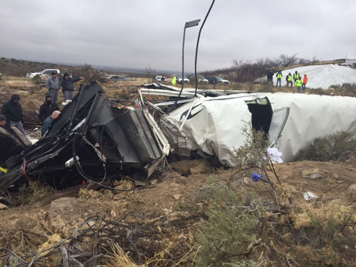 A county sheriff says at least 10 people are dead after a bus carrying state prisoners skidded off an icy highway overpass in West Texas, slid down an embankment and collided with a train.