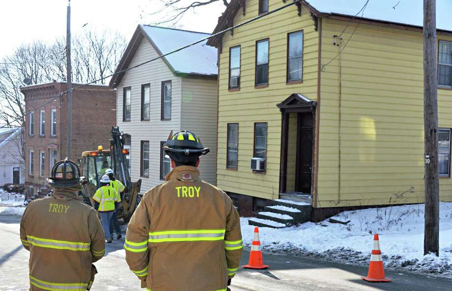Troy firefighters stand watch as National Grid crews work to stem a gas leak at 41 Brunswick Ave., right, Wednesday Jan. 14, 2015, in Troy, NY.  (John Carl D'Annibale / Times Union) Photo: John Carl D'Annibale