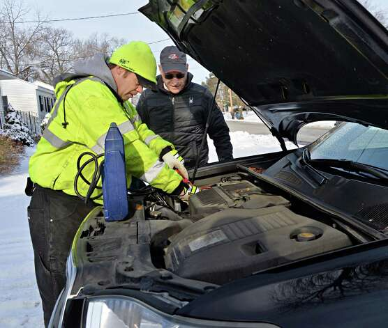 AAA fleet driver Michael Nolan, left, jumps starts Jeff Schafran's car at his home Wednesday, Jan. 14, 2015, in Colonie, NY.  (John Carl D'Annibale / Times Union) Photo: John Carl D'Annibale