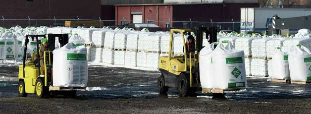 Despite frigid temperatures, stevedore Matthew Kelly, left, and John McEwan, right, load some of the 3000 one ton bags of calcium chloride to be shipped to Canada by truck Wednesday, Jan. 14, 2015, at the Port of Albany in Albany, N.Y. (Skip Dickstein/Times Union) Photo: SKIP DICKSTEIN