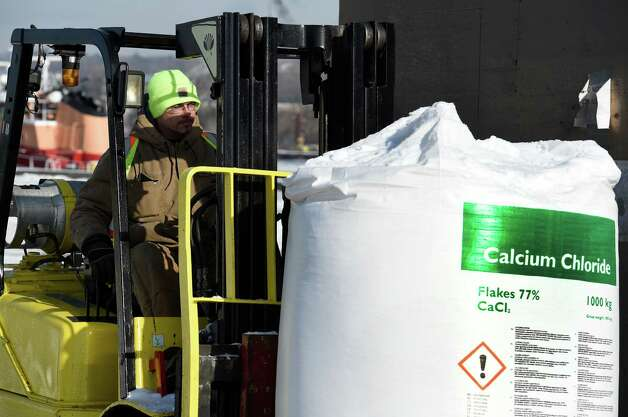 Despite frigid temperatures, stevedore Matthew Kelly loads some of the 3000 one ton bags of calcium chloride to be shipped to Canada by truck Wednesday, Jan. 14, 2015, at the Port of Albany in Albany, N.Y. (Skip Dickstein/Times Union) Photo: SKIP DICKSTEIN