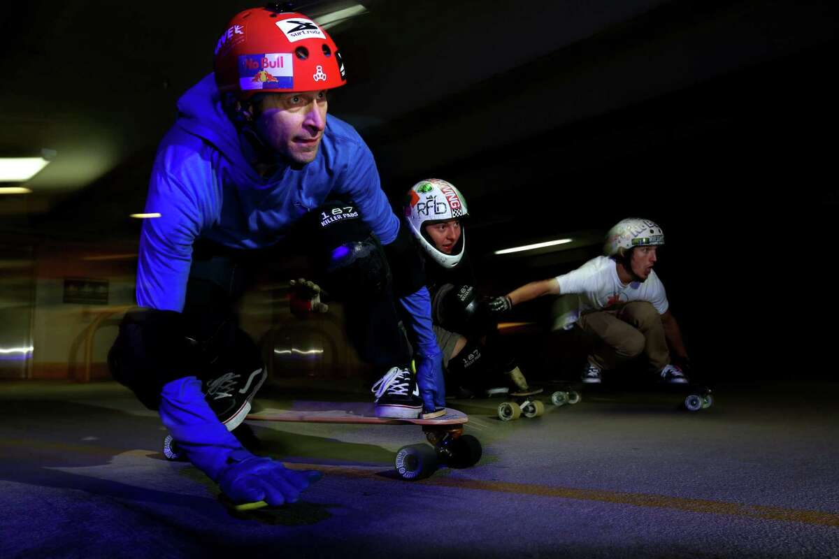 Damen Sistrunk, 43, left, along with Team No Bull and other longboard skaters ride in a parking garage, where most longboarders skate because Houston is too flat for speed.