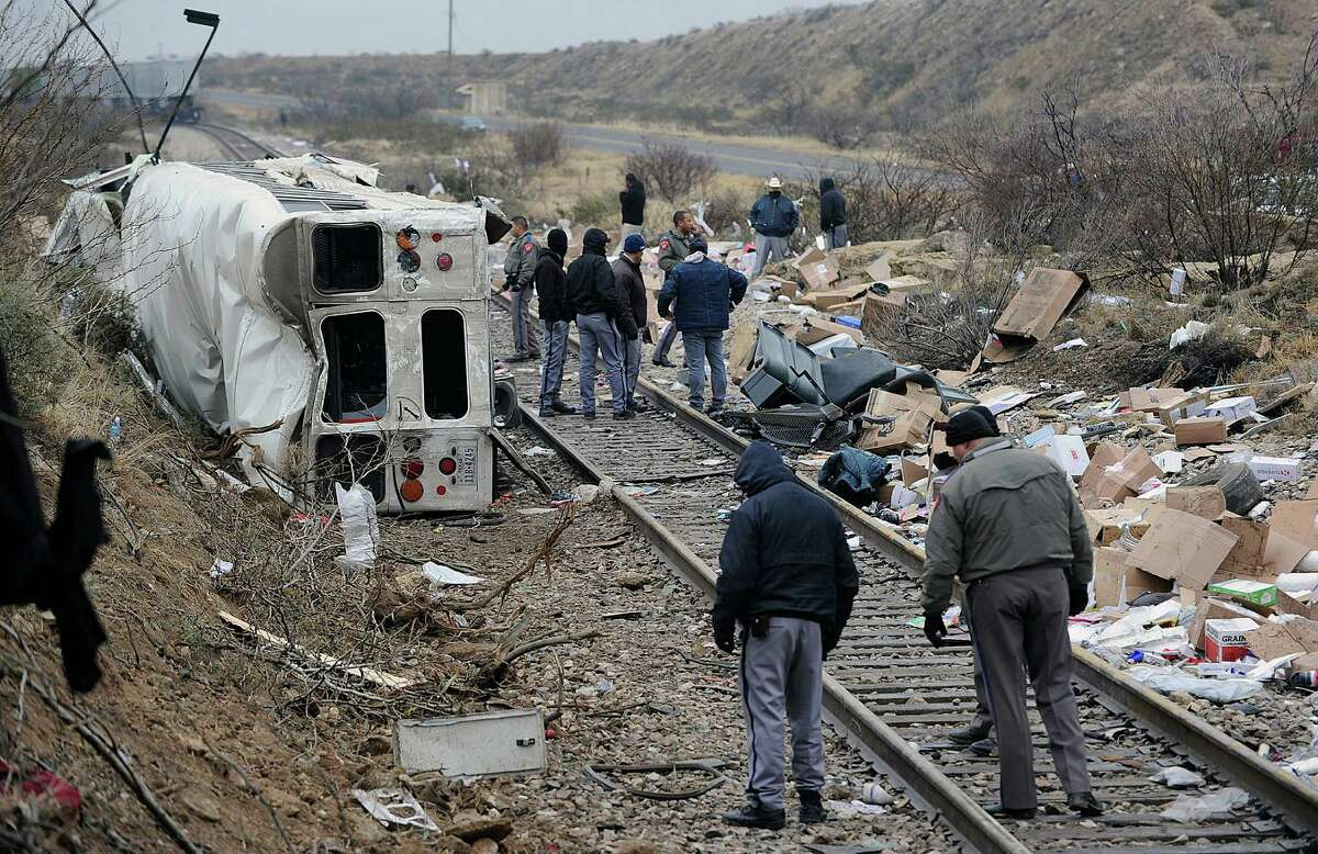 A bus carrying prison inmates and corrections officers rests on its side after sliding off an overpass and hitting a freight train in Penwell, Texas. Investigators probe the scene Authorities investigate the scene of a prison bus crash, Wednesday, Jan. 14, 2015, in Penwell, Texas. Law enforcement officials said the bus, carrying prisoners and corrections officers, fell from an overpass in West Texas and collided with a passing freight train, killing at least 10 people. (AP Photo/Odessa American, Mark Sterkel)