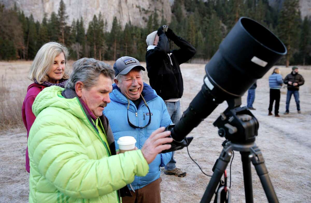 Photographer Tom Evans, (Left) of elcapreport.com points out the climbers to Mike Caldwell the father of climbers Tommy Caldwell on the face of El Capitan in Yosemite National Park, Calif. as Caldwell and Kevin Jorgeson attempt to free climb the Dawn Wall route on Wednesday January 14, 2015.