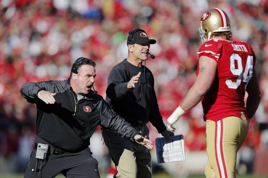 Defensive line coach Jim Tomsula  and head coach Jim Harbaugh congratulate defensive tackle Justin Smith #94 of the San Francisco 49ers after a sack on quarterback Russell Wilson of the Seattle Seahawks for a loss of nine yards in the first quarter on December 8, 2013 at Candlestick Park in San Francisco, California. Photo: Brian Bahr, Getty Images