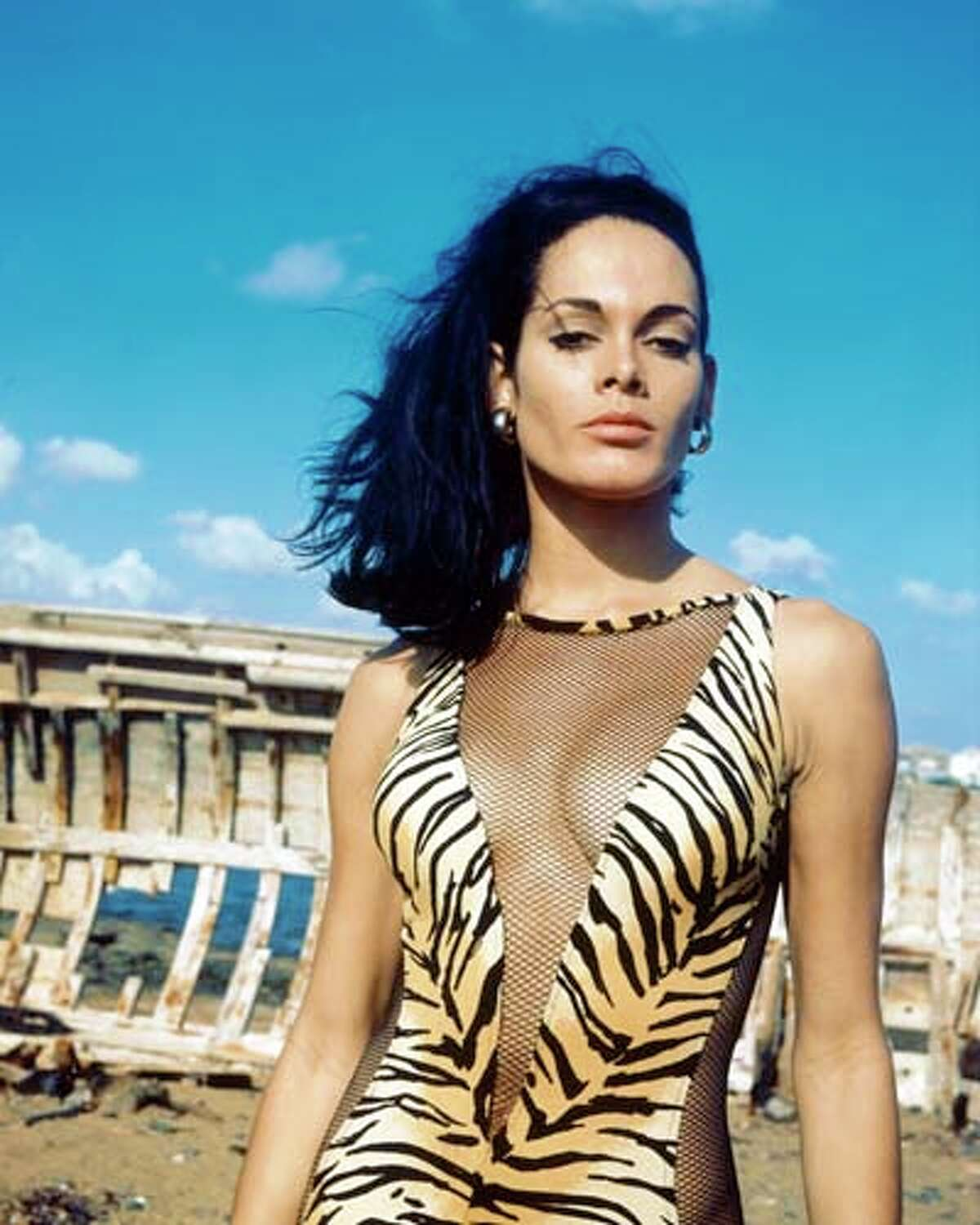 Martine Beswick, British actress and model, wearing a tiger skin print swimsuit with fishnet cut-outs in a 'V' across the front as well as up the side.