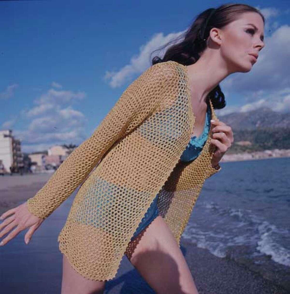 A blue bikini with a gold mesh cardigan.