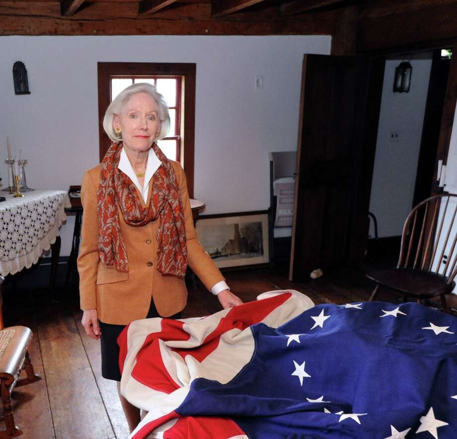 Davidde Strackbein, chair of the 375th Anniversary Committee, with a Betsy Ross replica flag of United States of America, inside historic Putnam Cottage at 243 E. Putnam Ave., Greenwich, Conn., Wednesday, Jan. 14, 2015. Greenwich is celebrating the 375th anniversary of its founding. On Sunday, Feb. 22, the Daughters of the American Revolution will provide a re-enactment at Putnam Hill Park featuring Gen. Israel Putnam's escape from invading British forces in 1779. Town officials will also rededicate Putnam Hill Park and there will be public tours of Putnam Cottage. Photo: Bob Luckey / Greenwich Time