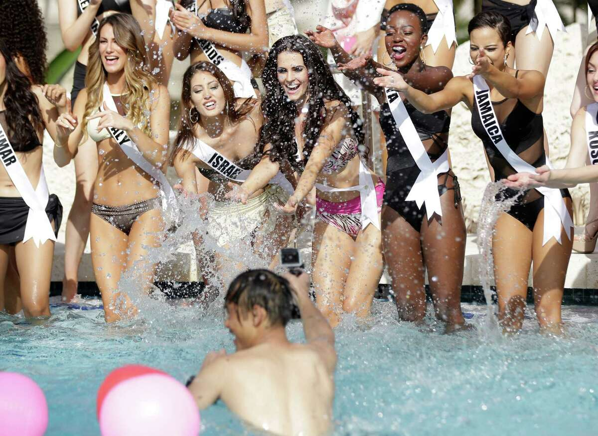 Miss Universe contestants Valentina Bonariva, of Italy, left, Doron Matalon, of Israel, Marcela Chmielowska, of Poland, Gaylyne Ayugi, of Kenya, and Kaci Fennell, of Jamaica, splash water at a photographer during the Yamamay swimsuit runway show, Wednesday, Jan. 14, 2015, in Doral, Fla. The Miss Universe pageant will be held Jan. 25 in Miami.