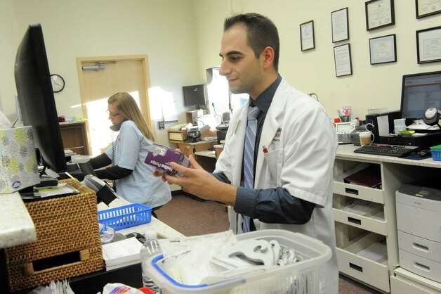 Pharmacist pharmacy manager David Laurenzo fills a prescription at the Market Bistro by Price Chopper pharmacy on Wednesday, Jan. 14, 2015 in Colonie, N.Y. (Michael P. Farrell/Times Union) Photo: Michael P. Farrell / 00030208A