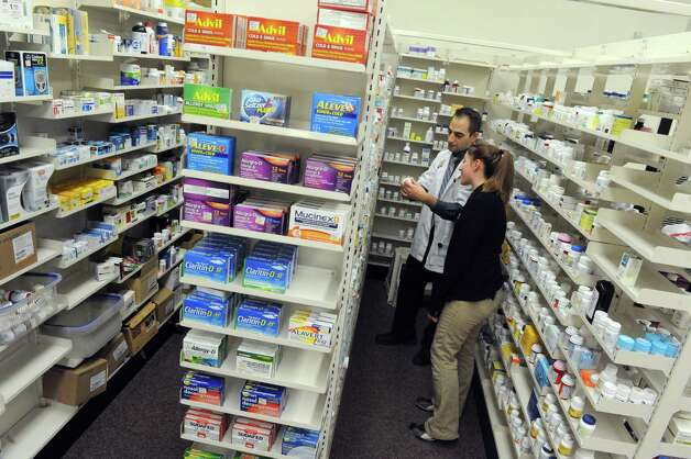 Pharmacist and pharmacy manager David Laurenzo and pharmacy clerk Samantha Smith fill a prescription at the Market Bistro by Price Chopper pharmacy on Wednesday, Jan. 14, 2015 in Colonie, N.Y. (Michael P. Farrell/Times Union) Photo: Michael P. Farrell / 00030208A