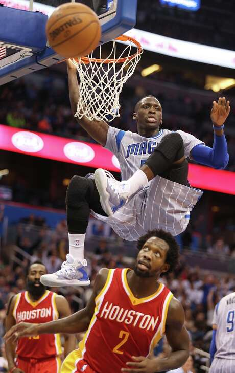 It's time for Pat Beverley (2) to look out below as the Magic's Victor Oladipo completes an acrobatic dunk Wednesday night for two of his game-high 32 points. Photo: Stephen M. Dowell, MBO / Orlando Sentinel