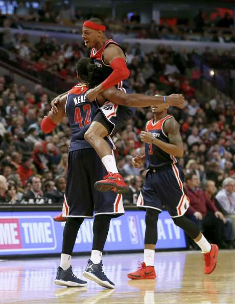 Paul Pierce leaps into Nene's arms after the Brazilian hit a 3-pointer late in the Wizards' victory. Photo: Charles Rex Arbogast, STF / AP
