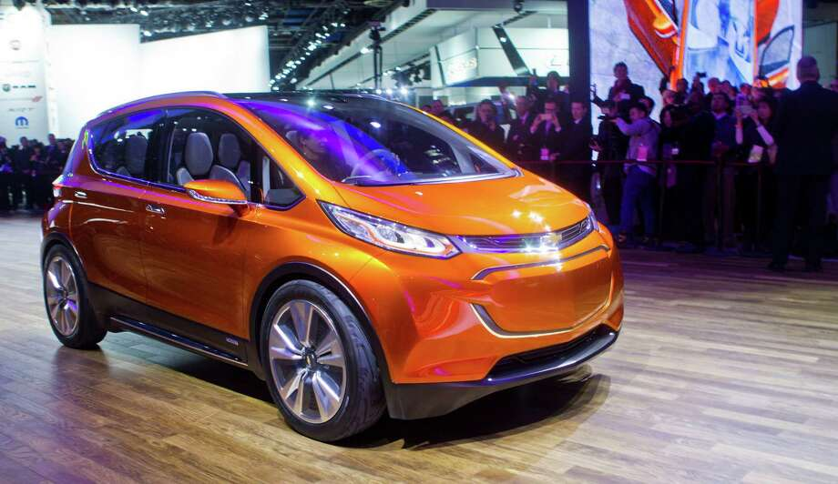FILE - In this Jan. 12, 2015 file photo, the Chevrolet Bolt EV electric concept vehicle is driven onto the stage at a presentation during the North American International Auto Show, in Detroit. The Bolt concept, an electric car with a 200-mile range, could go on sale by 2017. (AP Photo/Tony Ding, File) Photo: Tony Ding, FRE / FR143848 AP