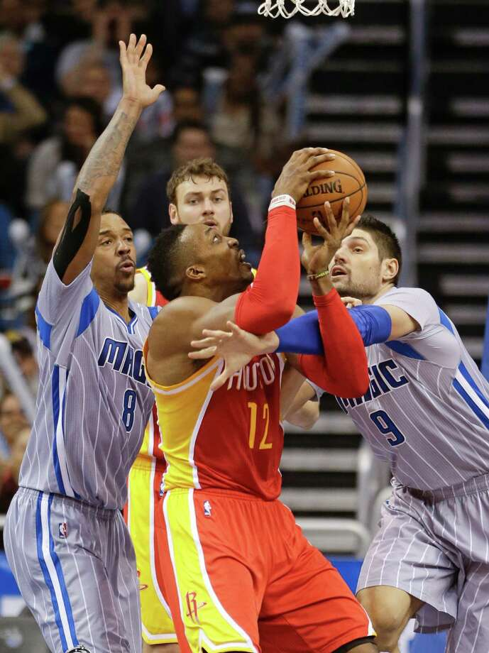 Dwight Howard, center, draws the attention of the Magic's Channing Frye, left, and Nikola Vucevic, with Vucevic being called for a foul. Howard had 23 points, but that was offset by 25 from Vucevic, his Orlando counterpart. Photo: John Raoux, STF / AP