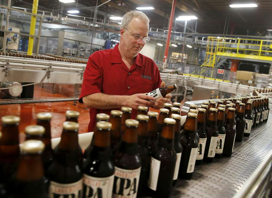 Lagunitas Brewing CEO Tony Magee examines a batch of IPA coming out of the bottling area in Petaluma, Calif. Craft brew sensation Lagunitas Brewing Company has dropped its trademark infringement lawsuit against fellow brewer Sierra Nevada Brewing Wednesday January 14, 2015. Photo: Brant Ward, The Chronicle