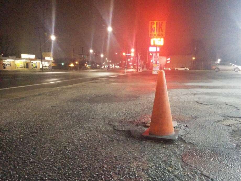 Two cones mark the spot where an electrical wiring short caused asphalt covering it to heat up to about 300 degrees. Photo: Jacob Beltran/San Antonio Express-News