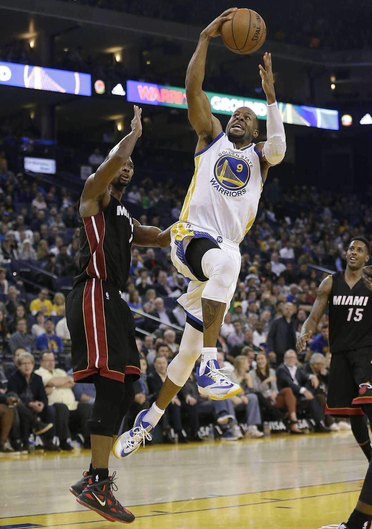 Golden State Warriors forward Andre Iguodala (9) shoots against Miami Heat forward Chris Bosh during the second half of an NBA basketball game in Oakland, Calif., Wednesday, Jan. 14, 2015. The Warriors won 104-89. (AP Photo/Jeff Chiu)