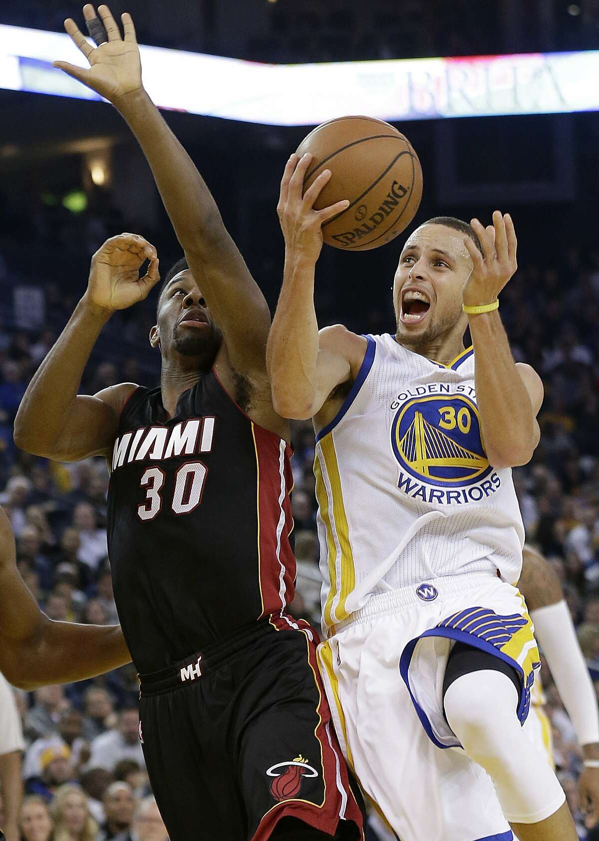 Golden State Warriors guard Stephen Curry shoots against Miami Heat guard Norris Cole during the second half of an NBA basketball game in Oakland, Calif., Wednesday, Jan. 14, 2015. The Warriors won 104-89. (AP Photo/Jeff Chiu)