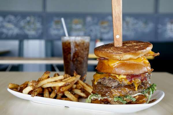 The Detention burger with two applewood smoked bacon grill cheeses used as a bun for two beef patties, each topped with cheddar, onions at Bernie's Burger Bus restaurant Wednesday, Sept. 17, 2014, in Houston. ( James Nielsen / Houston Chronicle )