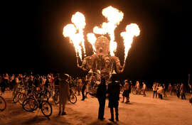 Burners enjoy the 2014 Burning Man festival with its drum circles, decorated art cars, guerrilla theatrics and colorful theme camps.