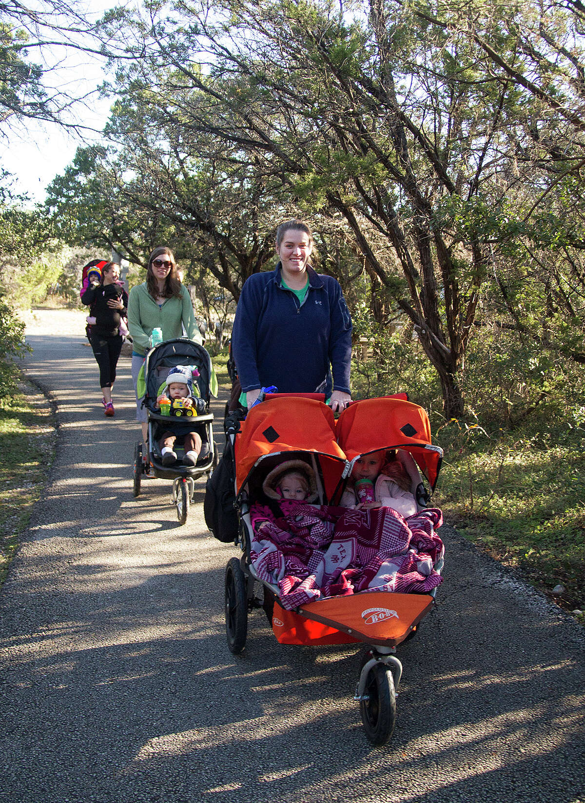 Katie Edge with her daughters Bailey, 1, and Isabelle, 3, on a three-mile hike with No Excuse Moms, a San Antonio fitness group for moms, Sunday, Jan. 4, 2015 at Eisenhower Park. Katie has lost 30 pounds since joining the group in September.