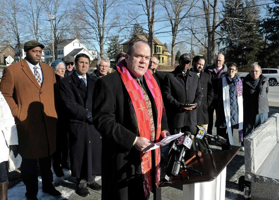 """Reverend  Matt Crebbin, of the Newtown Congregational Church, speaks in front of Edmund Town Hall, in Newtown, about the national gun safety effort of the interfaith group,  """"Do Not Stand Idly By"""". The group gathered in Newtown to ask the National Shooting Sports Foundation (NSSF), of Newtown, to help end the campaign aimed at keeping personalized, or """"smart guns"""", off the market. On Thursday, January 15, 2015, in Newtown, Conn. Personalized guns are ones that have built in authentication technology which prevents firing by unauthorized users. Photo: H John Voorhees III / The News-Times"""