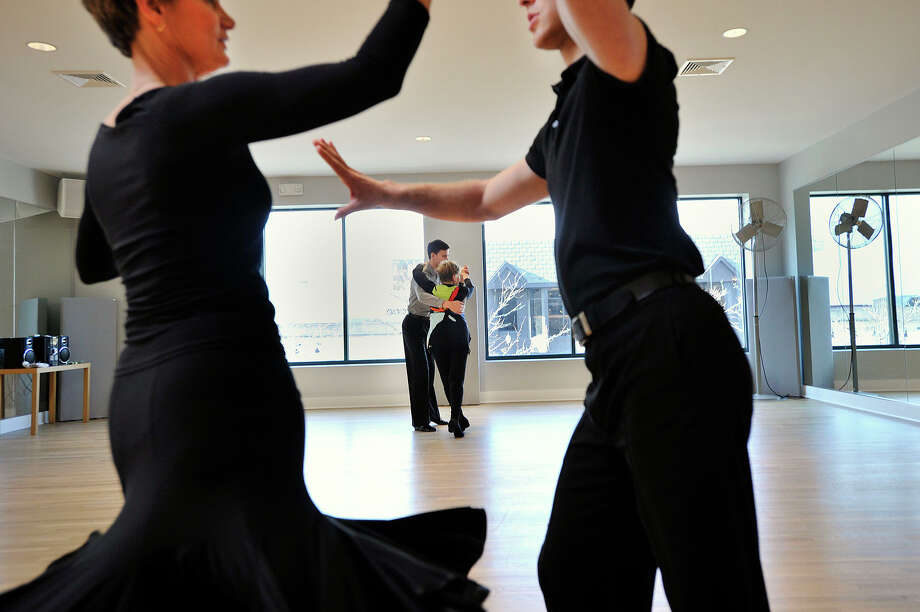 Dance instructor Sergey Vasilyev works with Lenore Rich, in background, as fellow dance instuctor Shane Jensen, right, and Barbara Tormondsen work on their dance moves during individual dance lessons at Metropolitan Dance Center in Stamford, Conn., on Thursday, Jan. 15, 2015. The dance studio recently relocated to their second floor location on Bedford Street. Photo: Jason Rearick / Stamford Advocate