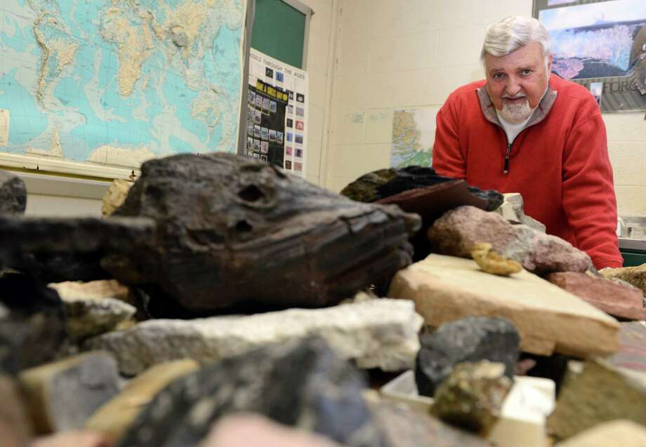 "John Nicholas, also known as ""Dr. Rock,"" a University of Bridgeport geology professor, stands over his collection of rocks in his classroom in Charles Dana Hall on the university campus in Bridgeport, Conn. Photo: Autumn Driscoll / Connecticut Post"