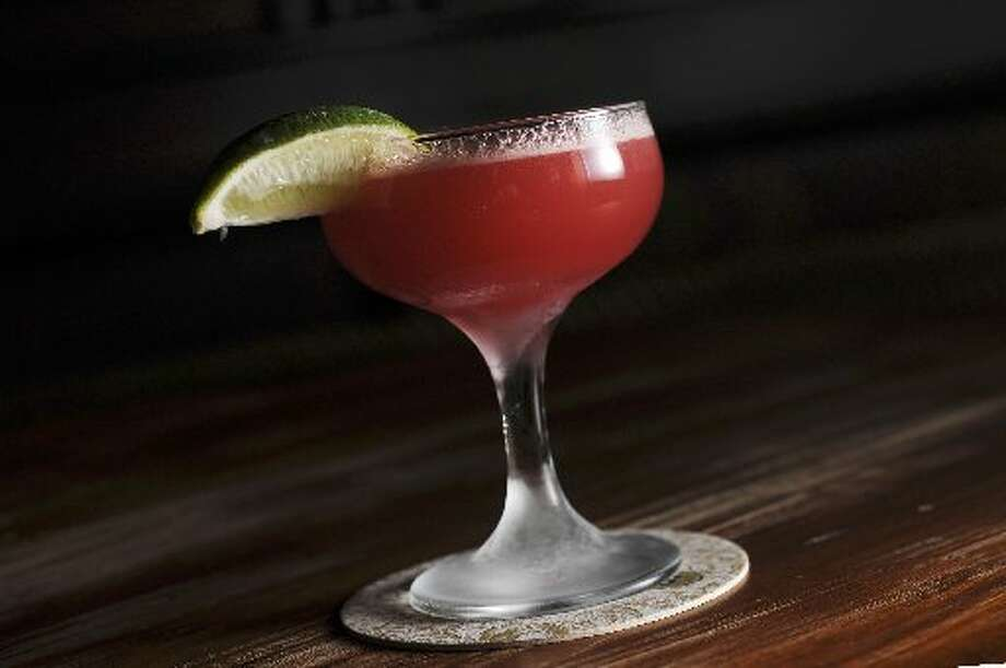 The Rosso Corsa: 2 ounces Woodford Reserve bourbon, 3/4 ounce house grenadine, 3/4 ounce lemon juice and two dashes of Peychaud's bitters. Combine ingredients in cocktail shaker, add ice, shake and strain into coupe. Garnish with lime wedge (optional). Photo: San Antonio Express-News
