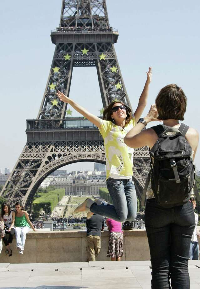 FILE - In this July 22, 2008 file photo, tourists take pictures in front of the Eiffel tower, in Paris. A strong U.S. dollar is making world travel cheaper for Americans in 2015. (AP Photo/Francois Mori, File) ORG XMIT: MER2015010518020654 Photo: FRANCOIS MORI / AP