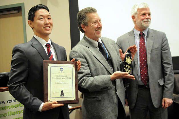 Shane Son, left, and William Hichak, center, of Columbia University hold the award for the school's innovative on-site recycling program as they pose with DEC Commissioner Joe Martens during the 11th Annual New York State Environmental Excellence Awards ceremony on Wednesday, Jan. 14, 2015, at SUNY Polytechnic Institute in Albany, N.Y. (Cindy Schultz / Times Union) Photo: Cindy Schultz, Albany Times Union / 00030193A