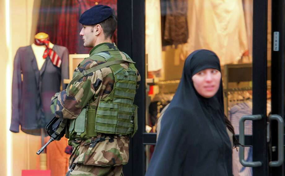 "A veiled woman walks past a soldier patroling in Roubaix as France announced an unprecedented deployment of thousands of troops and police to bolster security at ""sensitive"" sites. Home to Europe's largest Jewish and Muslim communities, France was shaken to the core by its bloodiest attacks in decades. The killings spotlighted the need for immigration reform. Photo: PHILIPPE HUGUEN /AFP /Getty Images / AFP"