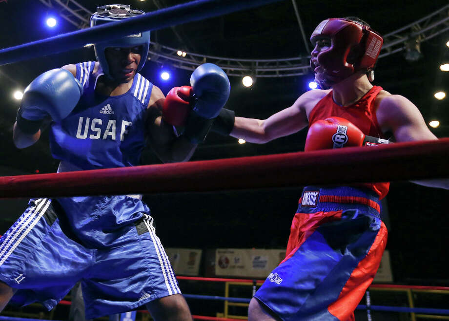 Tavarus Roberts (left) and Cresencio Ramos exchange punches during their open lightweight bout at the San Antonio Regional Golden Gloves tournament on Feb. 22, 2014 at Cowboys Dancehall. Ramos won by decision. Photo: Edward A. Ornelas /San Antonio Express-News / © 2014 San Antonio Express-News