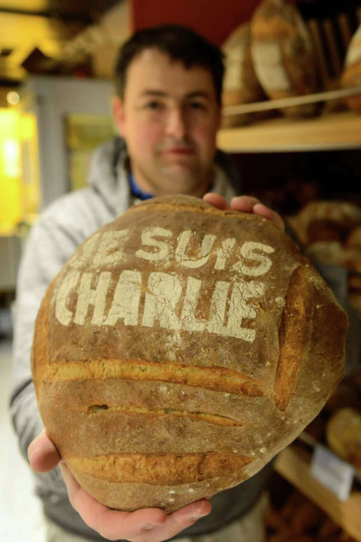 """Baker Pascal Clement holds a loaf of bread with """"Je suis Charlie"""" (I am Charlie) written on it in commemoration to the victims of Charlie Hebdo newspaper, Friday, Jan. 9, 2015, in Daillens, Switzerland. Masked gunmen stormed the Paris offices of the weekly newspaper that caricatured the Prophet Muhammad, methodically killing 12 people at the offices of the paper, Wednesday, including the editor, before escaping in a car. It was France's deadliest postwar terrorist attack. (AP Photo/Keystone, Laurent Gillieron)"""