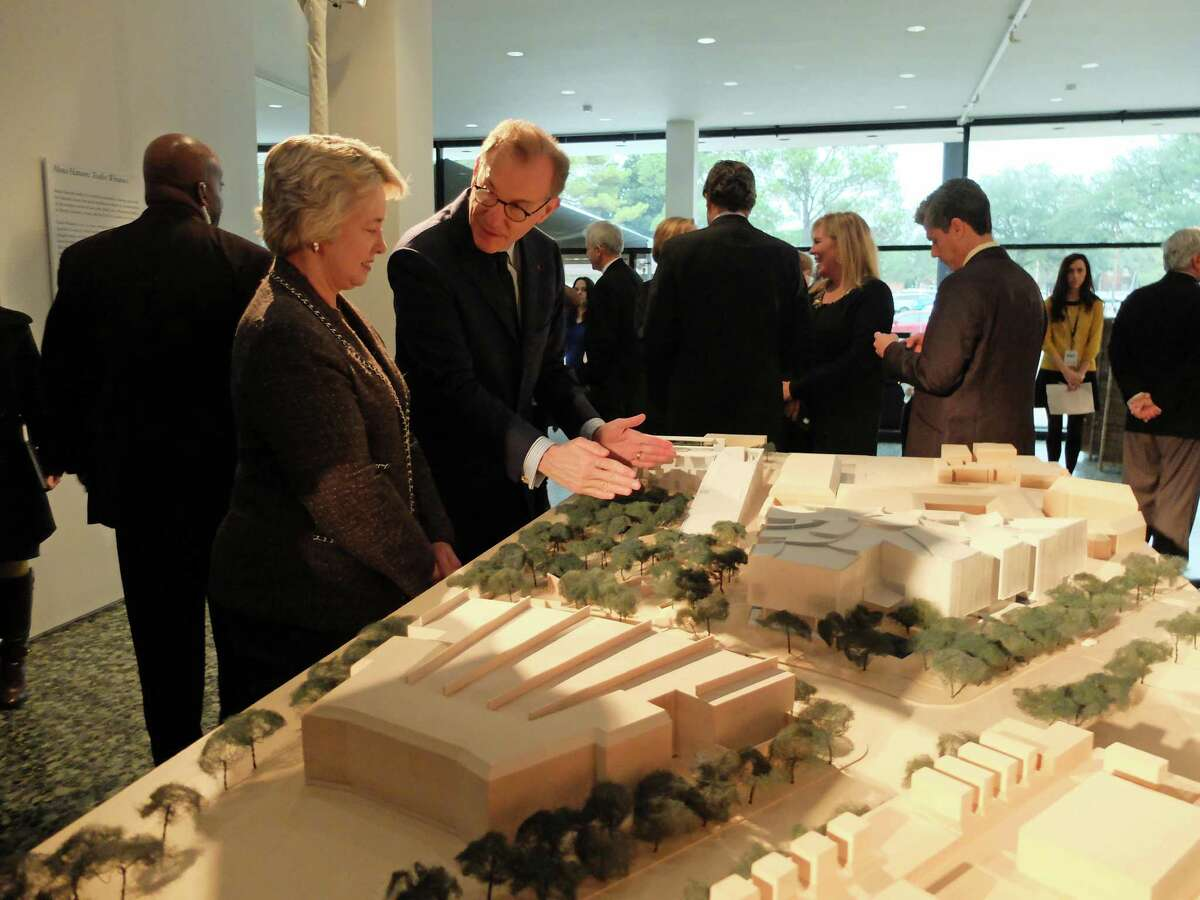 Mayor Annise Parker listens as Museum of Fine Arts, Houston director Gary Tinterow explains the model by Steven Holl Architects for the institution's Fayez S. Sarofim Campus. (Molly Glentzer / Houston Chronicle)