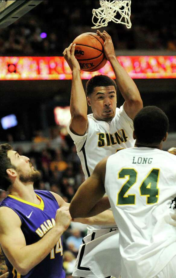 Siena's Javion Ogunyemi, center, controls the rebound during their basketball game against UAlbany on Saturday Dec. 13, 2014, at Times Union Center in Albany, N.Y. (Cindy Schultz / Times Union) Photo: Cindy Schultz / 00029816A
