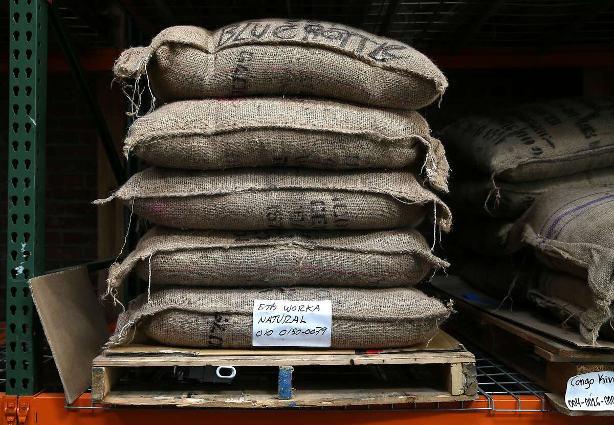 Burlap sacks of coffee beans, each weighing 60 kilograms, are stacked in the warehouse at the Blue Bottle Coffee roasting plant in Oakland, Calif. on Wednesday, Jan. 14, 2015
