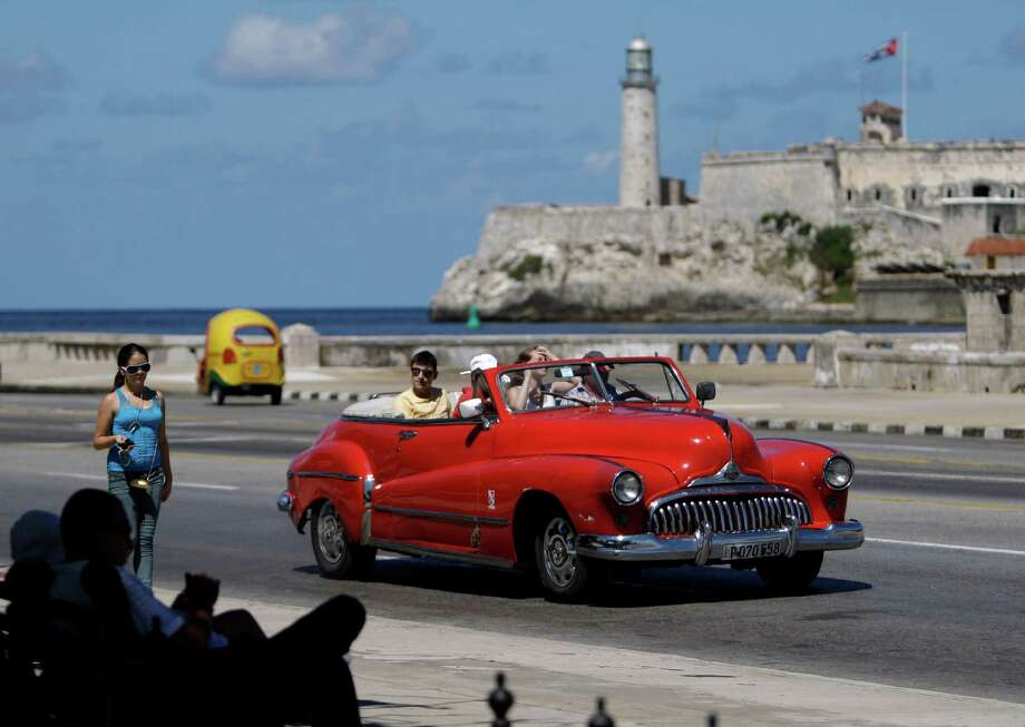 FILE - In this Oct 12, 2013 file photo, tourists ride in a classic American car on the Malecon in Havana, Cuba. A new set of U.S. government regulations takes effect Friday, Jan. 16, 2015, severely loosening the 50-decade long travel and trade restrictions for Cuba. (AP Photo/Franklin Reyes, File) ORG XMIT: NYBZ162 Photo: Franklin Reyes / AP