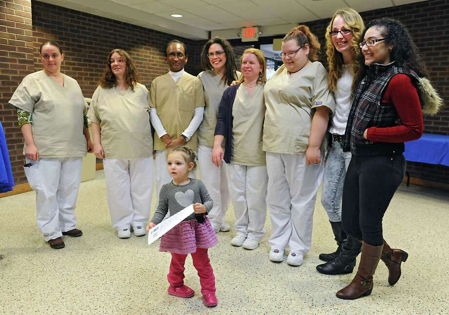 Paighten Feulner, 2, of Schenectady steals the spotlight during a group photo of graduates at a ceremony for the Health Profession Opportunity Grants (HPOG) program at Schenectady County Community College on Thursday, Jan. 15, 2015 in Schenectady, N.Y. The graduates have completed education and training to become certified nurse aides (CNA), home health aides (HHA), and personal care aides (PCA). (Lori Van Buren / Times Union) Photo: Lori Van Buren / 00030190A