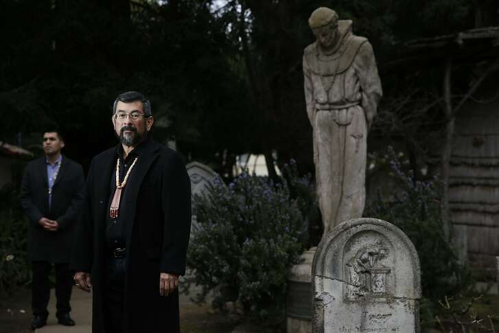 After news that Pope Francis will canonize Father Junipero Serra,  Asst. curator of the Mission Dolores museum Vincent Medina with museum curator Andrew Galvan, both Ohlone Indians, stand in the Mission Dolores cemetery  next to a statue of Junipero Serra on Thursday Jan. 15, 2015 in San Francisco, Calif.  Galvan said their are 5,700 Indian buried in unmarked graves there. He hopes soon more will be memorialized.