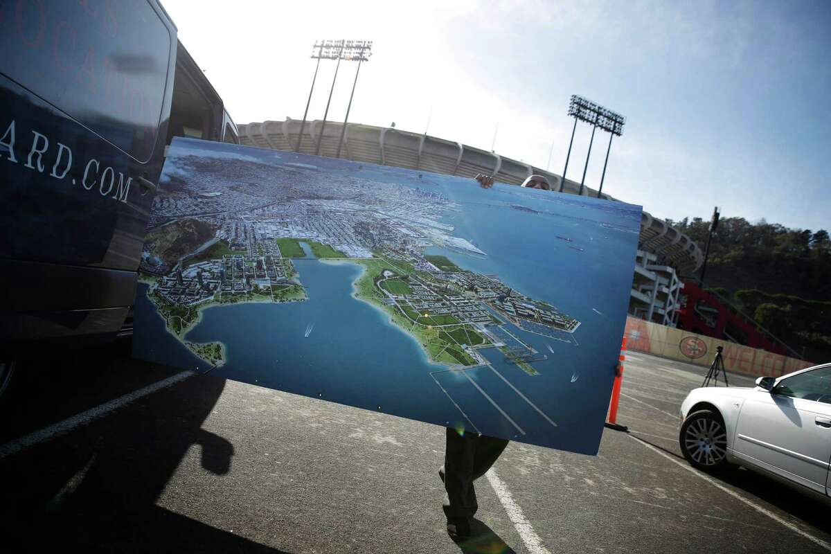 Shuttle driver Tadesse Dereje puts a rendering for the Candlestick Point development project into a vehicle after a news conference in the Candlestick Park parking lot on Nov. 17.