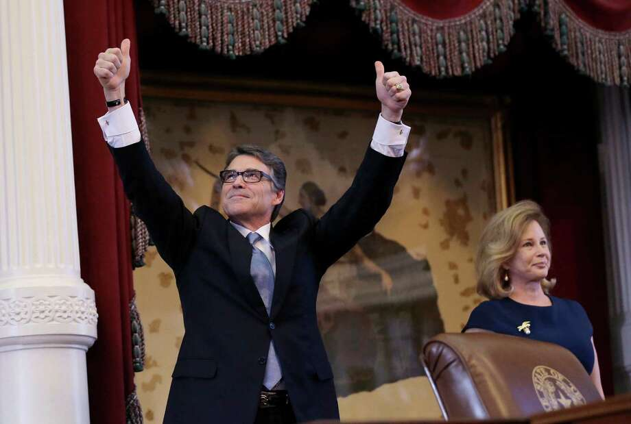 Outgoing Gov. Rick Perry acknowledges applause with his wife, Anita, before giving a farewell speech Thursday to a joint session of the Texas Legislature in Austin. Photo: Eric Gay, STF / AP
