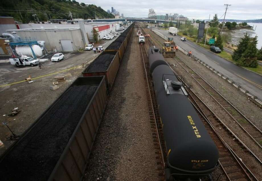 A coal train passes an oil train after tanker cars derailed in Magnolia in the spring of 2014.  The Whatcom County Council has slapped a moratorium on permits to export unrefined oil, natural gas and coal out of Cherry Point north of Bellingham.