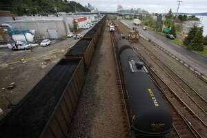 A coal train passes an oil train after tanker cars derailed in Magnolia last spring. In order to keep trains running, with limited regulation and transparency, the fossil fuel industry invested big bucks in re-electing key allies in the state Senate last November.
